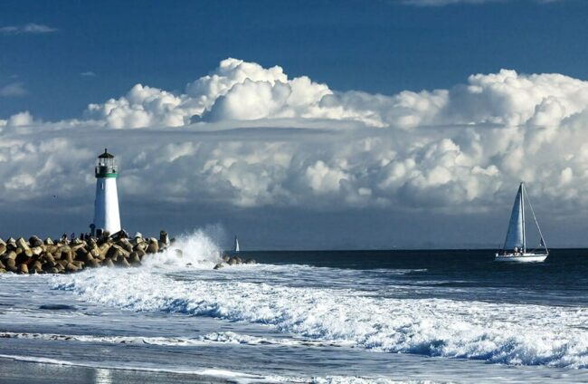 lighthouse and waves with sail boat