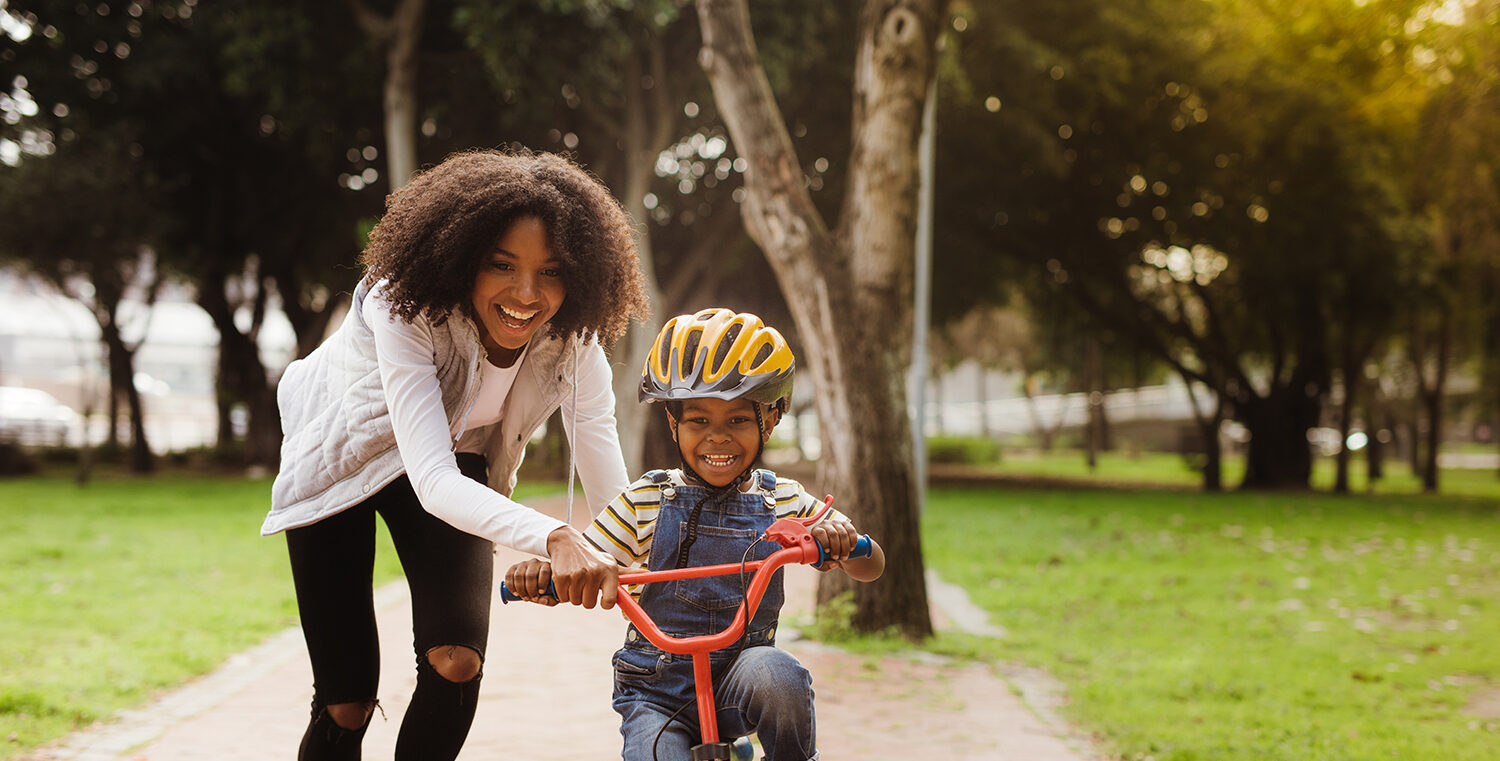 boy learning to ride a bike with his mother