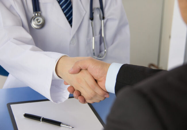 physician and business man shaking hands
